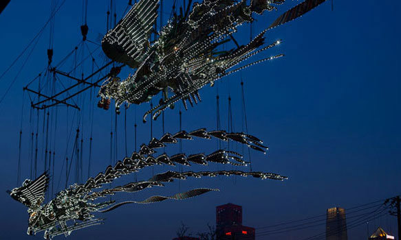 At MASS MoCA, the internally illuminated 12-ton birds are suspended mid-air inside the museum's football field-sized Building 5; dwarfing visitors, the male Phoenix Feng measures 90 feet long, while the female Huang reaches 100 feet in length, beak to (steel) tail feathers.