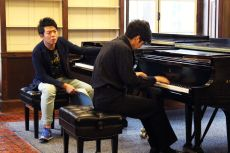 Pianist Lang Lang listens intently to his student's musical nuances.